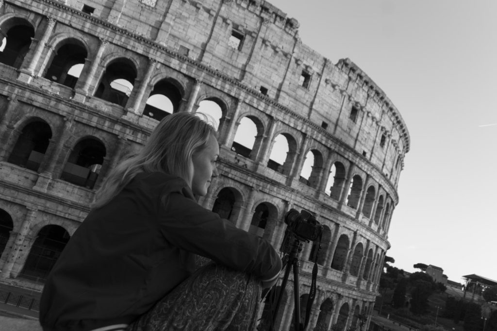 Young woman sitting in front of the Colosseum in Rome