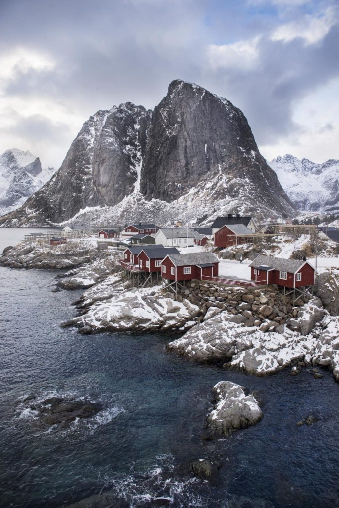 Red fisherman's cabins in front of mountains in Hamnøy in Lofoten