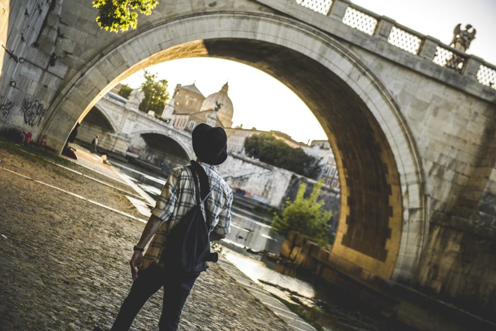 Man with hat walks under bridge along canal
