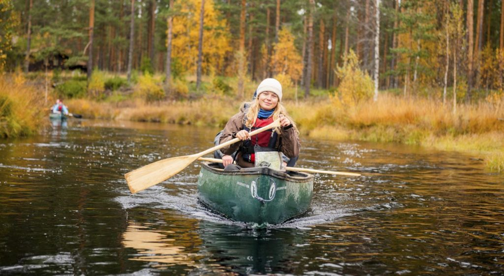 Young woman paddling in canoe
