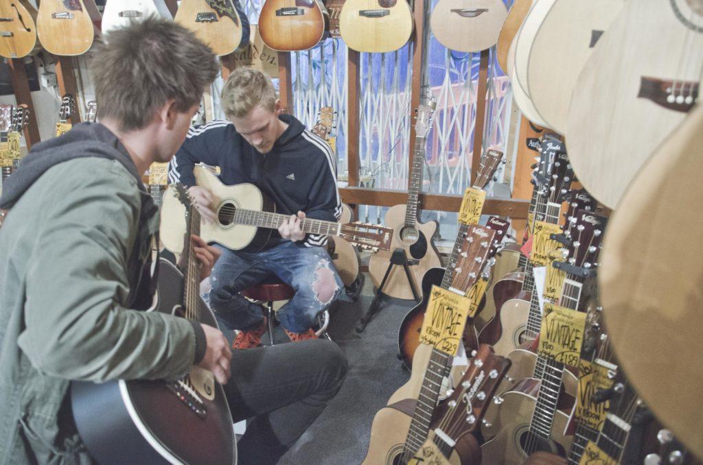 Musikere spiller gitar i musikkbutikk
