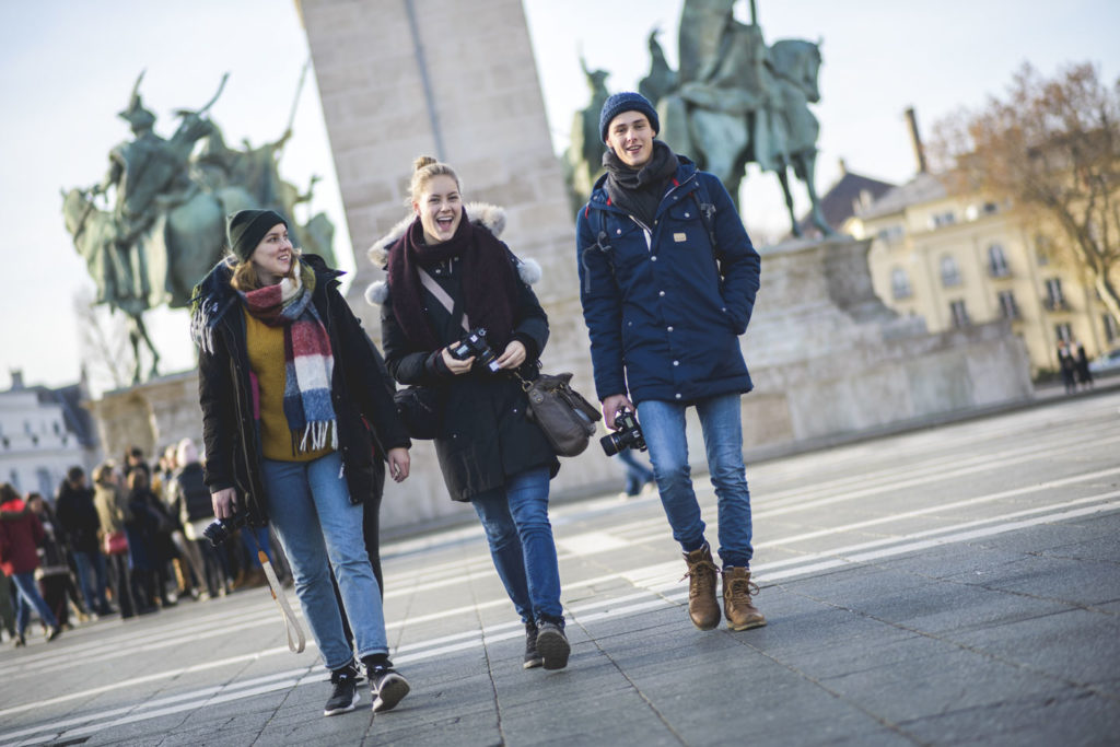 Three young people walk side by side in a big city