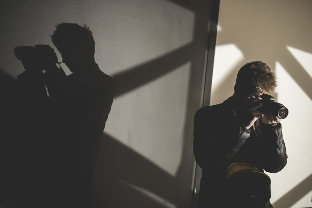 Photographer and geometric shadows on a wall