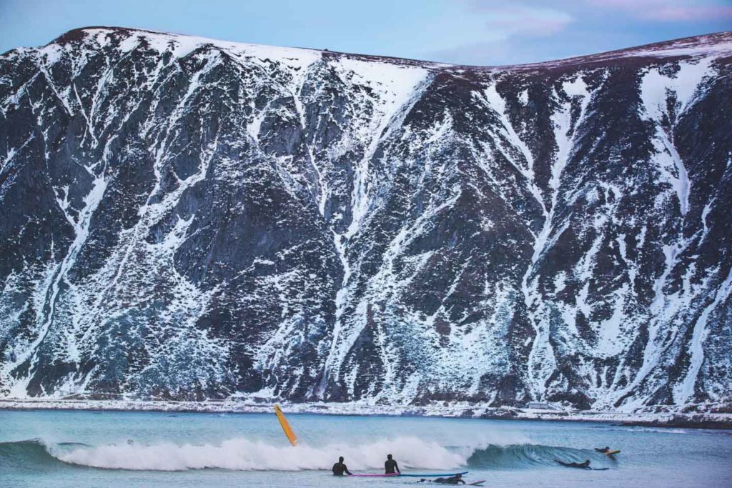 Surfers in the water in front of high snow-capped mountains at Flakstad in Lofoten