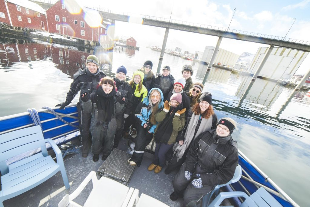 Smiling young people in the bow of a fishing boat drive into Svolvær