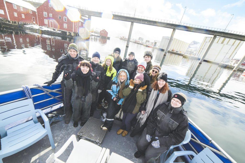 Smilende unge mennesker i baugen på en fiskebåt kjører inn i Svolvær