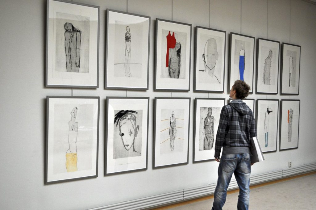 Boy looking at big pictures on a gallery wall