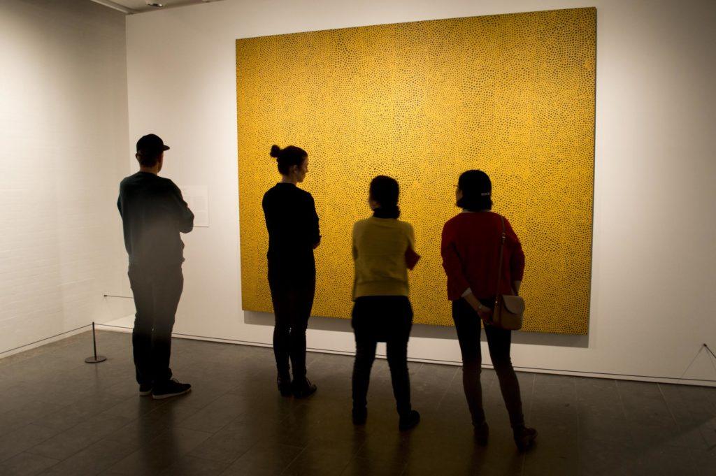 Mennesker studerer et stort gult bilde i et galleri
