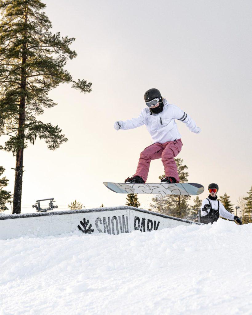 Ung kvinne hopper mot en rail på snowboard