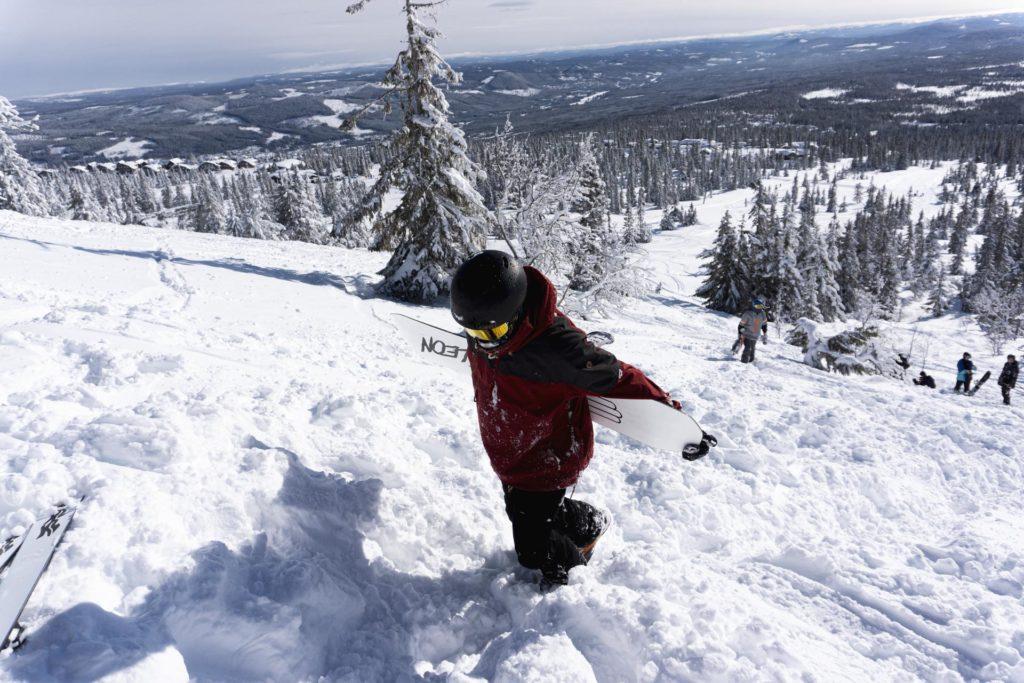 Snowboarder går oppover bakke