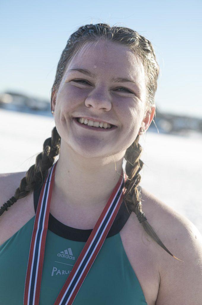 Ung kvinne smiler med medalje