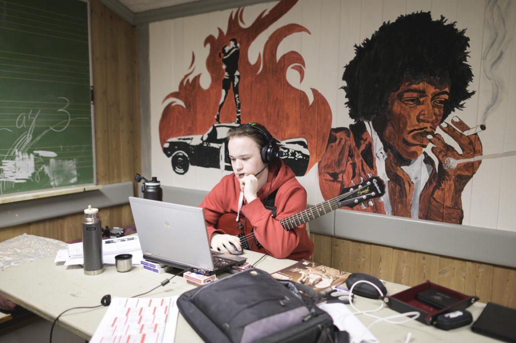 Ung mann med gitar og datamaskin