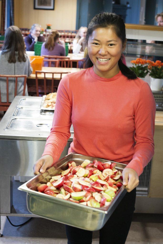 Ung kvinne smiler med masse epler
