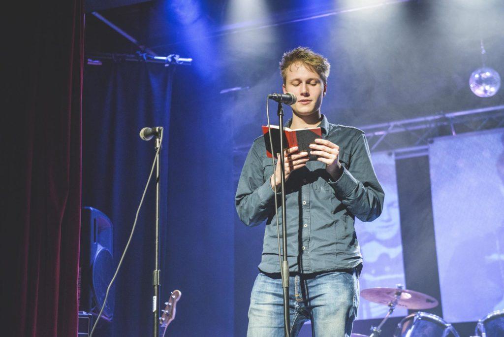 Ung mann leser dikt på scenen