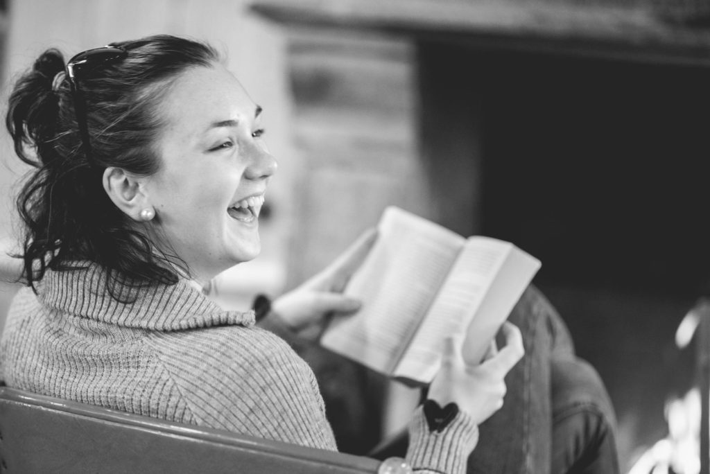 Young woman reading book and smiling