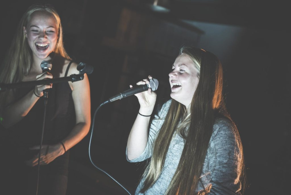 Two young women are singing karaoke