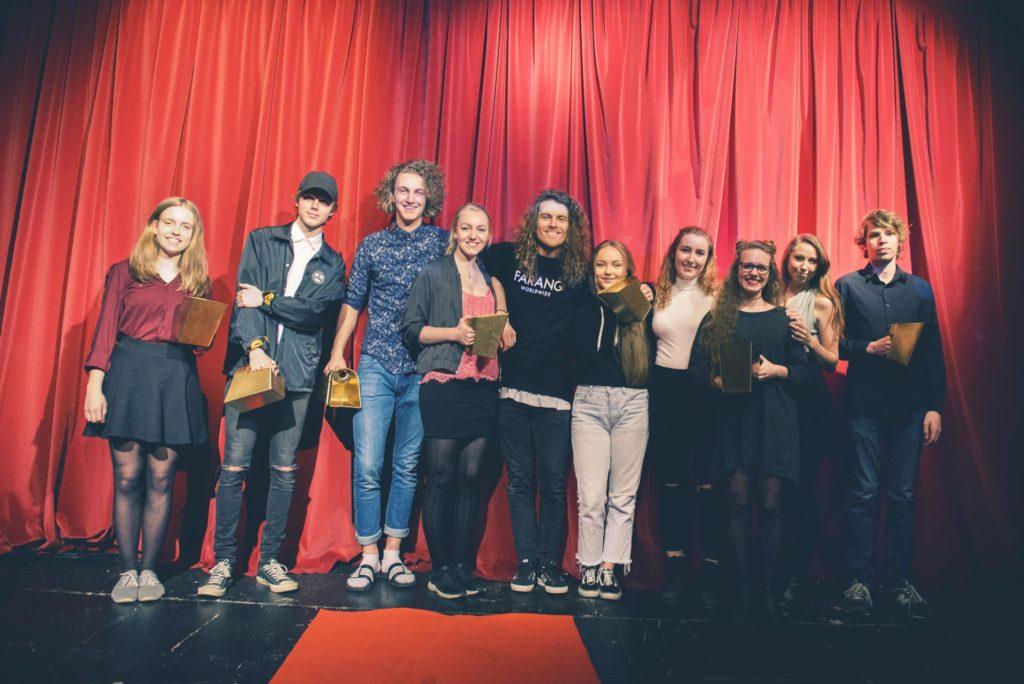 Gruppe unge mennesker poserer foran sceneteppe med filmpris
