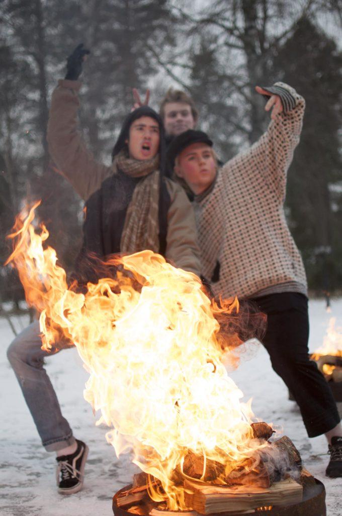 Tre unge mennesker bak et flammende bål i forbindelse med teateroppsetning
