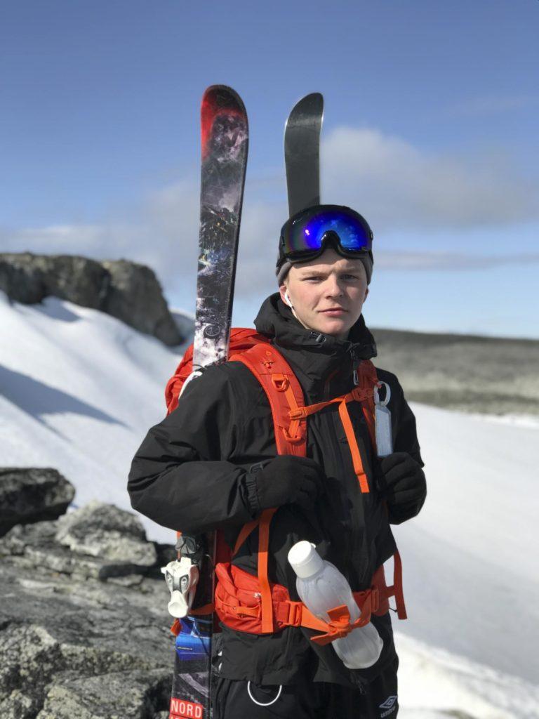 Ung mann på fjellet med ski festet på sekken