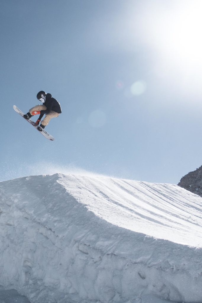Snowboarder grabs the board on a big jump