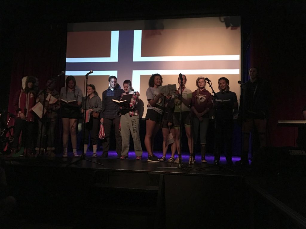 Young people on stage in front of the Norwegian flag