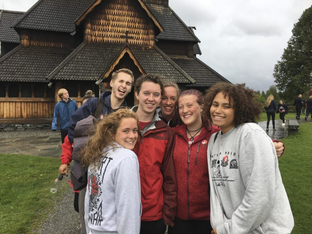 Group of young people in front of stave church