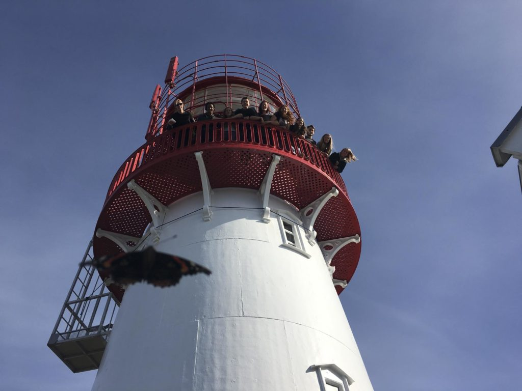Group of young people peeking over the edge of a lighthouse