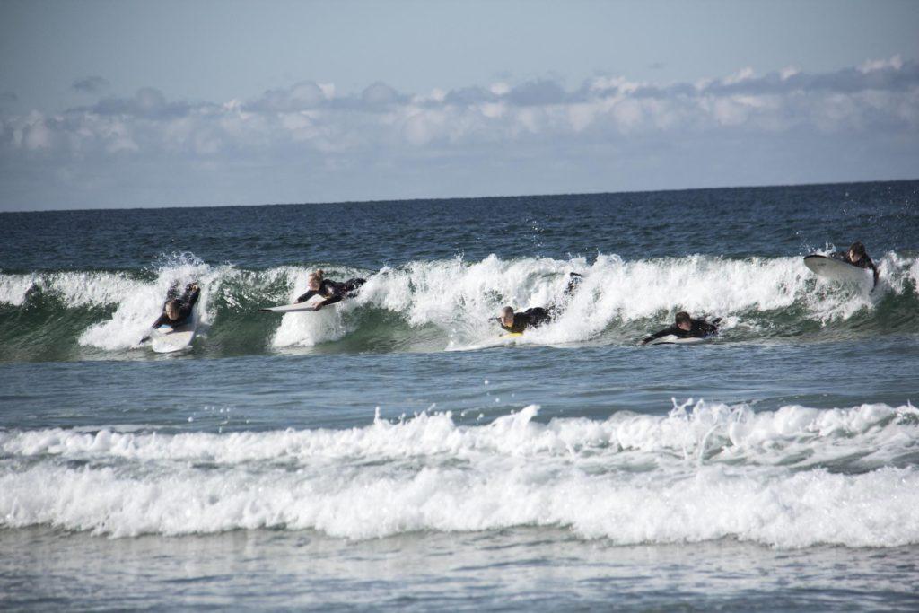 Surfere ligger på brett i bølge