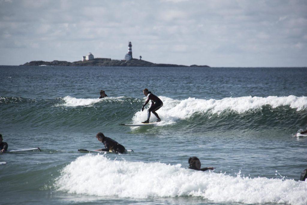 Surfer står på brett i bølge