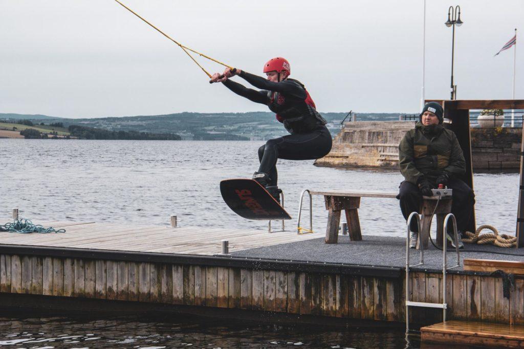 Ung mann prøver wakeboard kabelbane