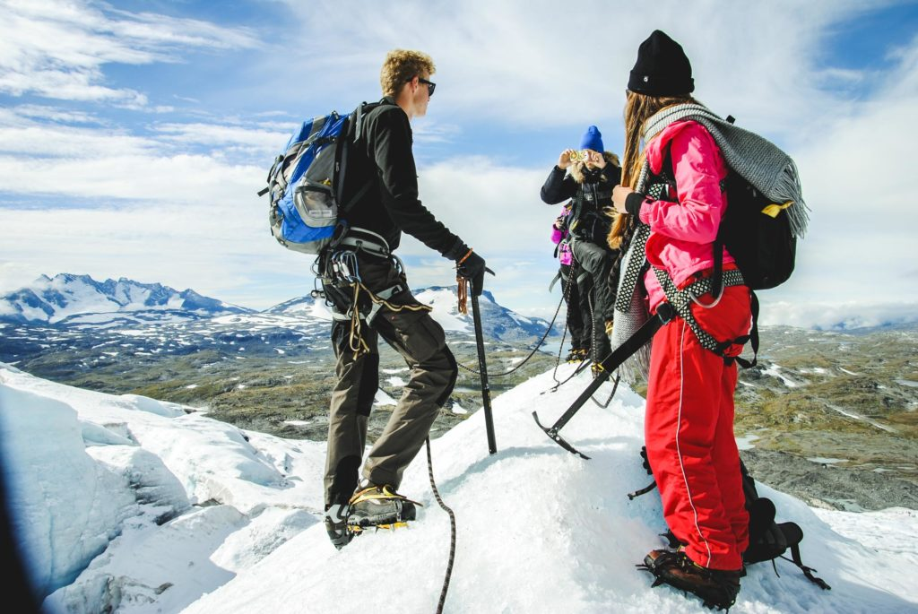 Three young people on top of snow-capped mountains