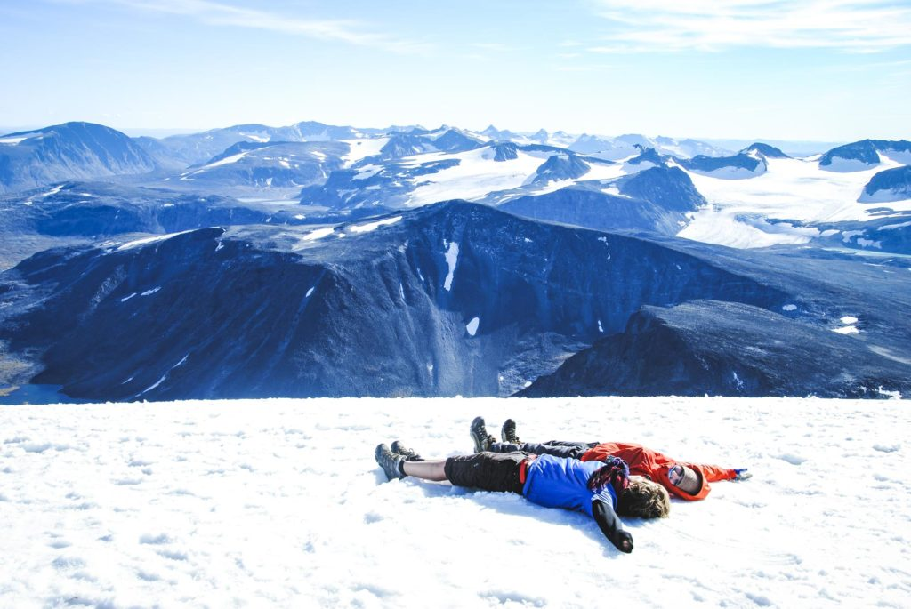 Young people relax on top of the mountain