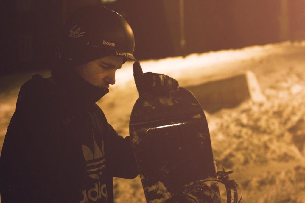 Ung mann poserer med snowboard