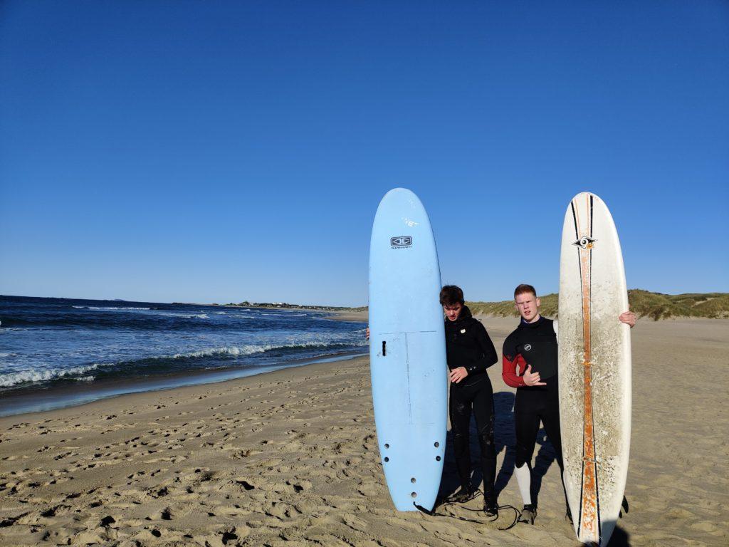 Unge menn poserer med surfebrett