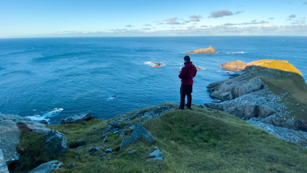 Person ser på utsikt over hav fra klippe