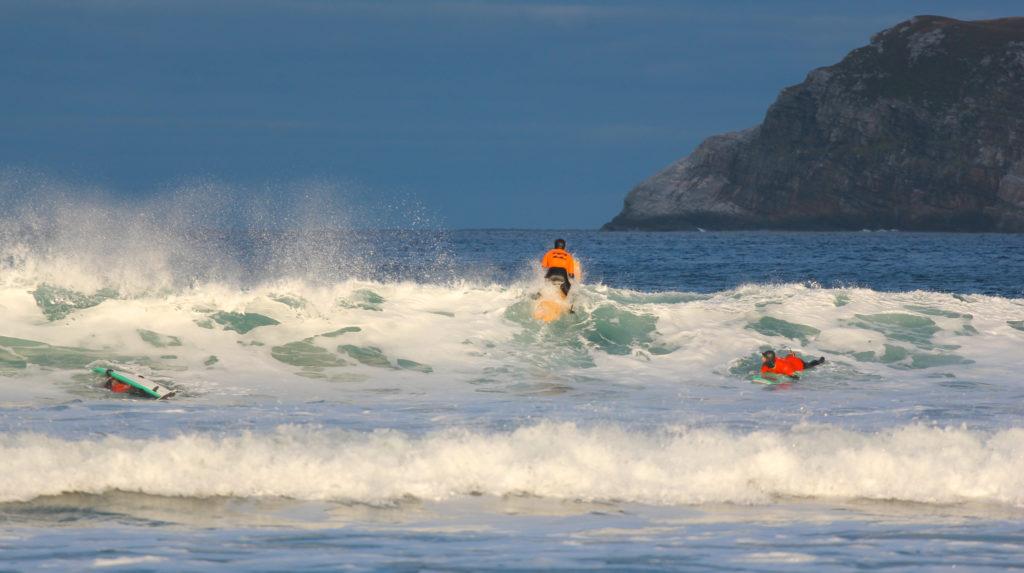 Surfer padler ut i bølger