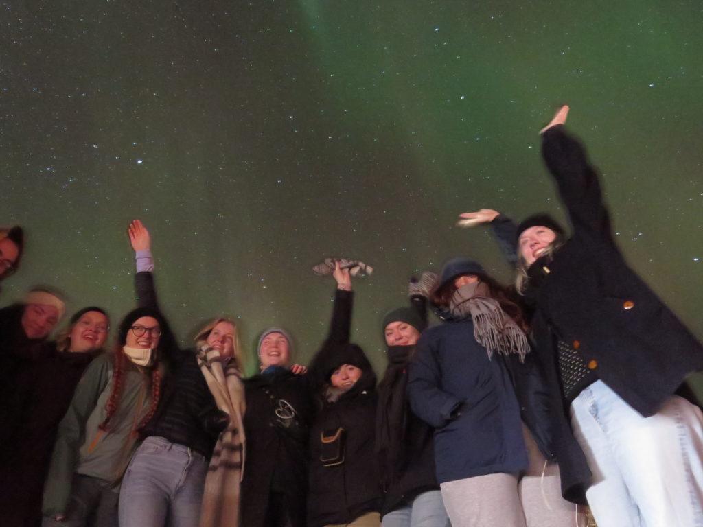 Gruppe unge mennesker under nordlys